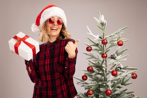 Lächelndes junges schönes mädchen, das in der nähe einen weihnachtsbaum trägt und eine weihnachtsmütze mit brille hält, die eine geschenkbox hält, die den daumen isoliert auf weißem hintergrund zeigt showing