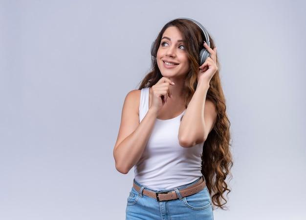Lächelndes junges schönes mädchen, das kopfhörer trägt, der musik hört, die auf der linken seite mit einer hand auf kopfhörer und einem anderen auf kinn mit kopierraum schaut