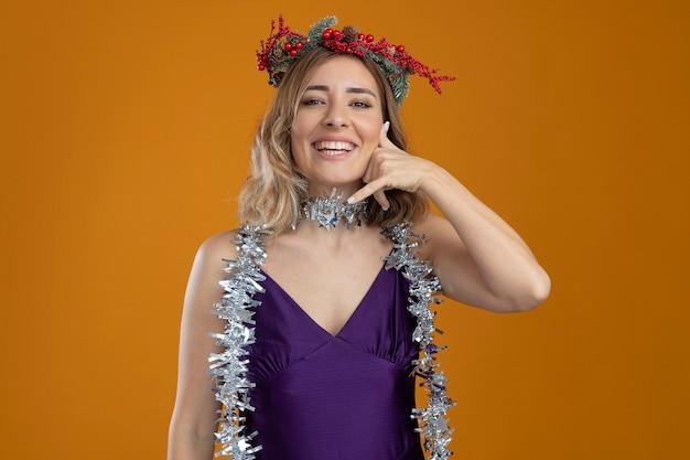 Lächelndes junges schönes mädchen, das lila kleid mit kranz trägt, das telefonanrufgeste lokalisiert auf braunem hintergrund zeigt