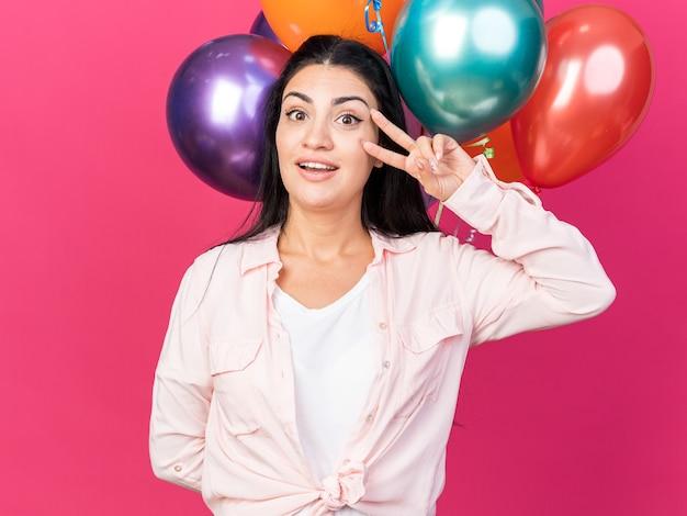 Lächelndes junges schönes mädchen, das luftballons hält, die friedensgeste zeigen
