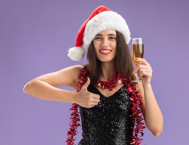 Lächelndes junges schönes mädchen, das weihnachtshut mit girlande auf hals hält, der glas champagner zeigt, der daumen oben auf lila hintergrund lokalisiert