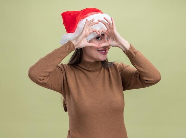Lächelndes junges schönes mädchen, das weihnachtshut trägt, das herzgeste lokalisiert auf olivgrünem hintergrund zeigt