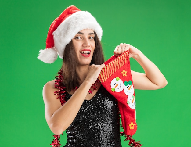 Lächelndes junges schönes mädchen, das weihnachtsmütze mit girlande am hals hält weihnachtssocke lokalisiert auf grüner wand trägt