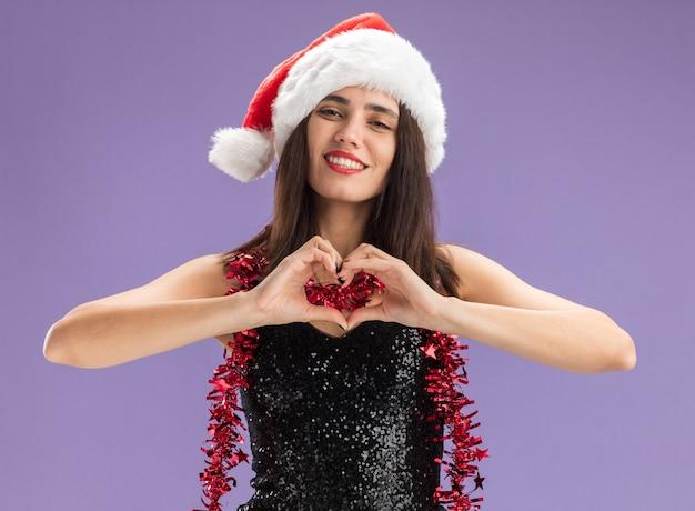 Lächelndes junges schönes mädchen, das weihnachtsmütze mit girlande am hals trägt, die herzgeste einzeln auf violettem hintergrund zeigt