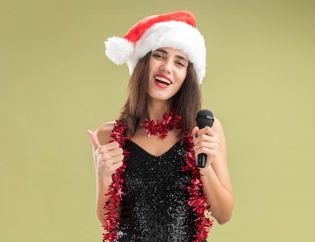 Lächelndes junges schönes mädchen, das weihnachtsmütze mit girlande am hals trägt und das mikrofon hält, das den daumen einzeln auf olivgrünem hintergrund zeigt