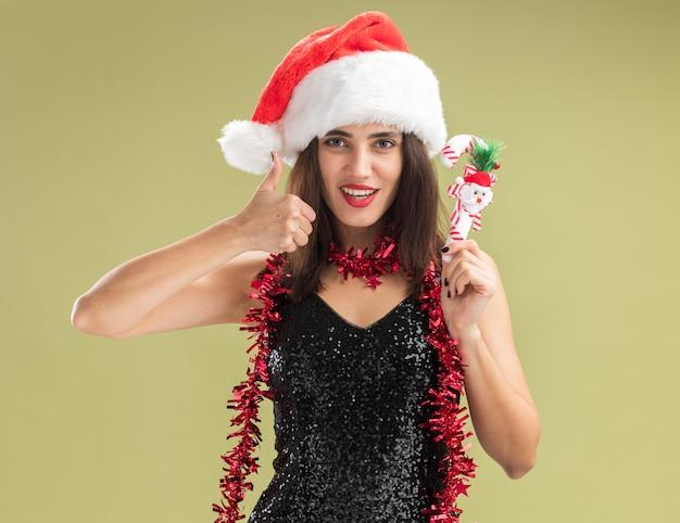 Lächelndes junges schönes mädchen, das weihnachtsmütze mit girlande am hals trägt und weihnachtsspielzeug hält, das den daumen einzeln auf olivgrünem hintergrund zeigt