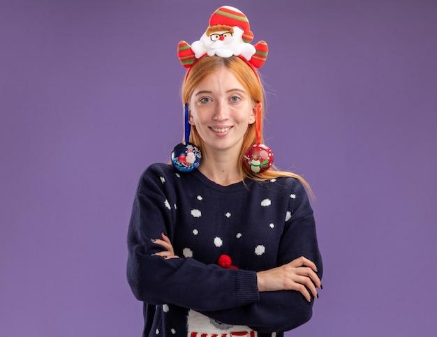 Lächelndes junges schönes mädchen, das weihnachtspullover mit weihnachtshaarbügel trägt hängte weihnachtskugeln auf ohrkreuzungshänden lokalisiert auf lila hintergrund