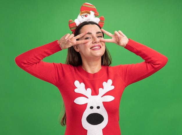 Lächelndes junges schönes mädchen, das weihnachtspullover mit weihnachtshaarreifen trägt, der friedensgeste einzeln auf grüner wand zeigt