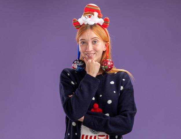 Lächelndes junges schönes mädchen, das weihnachtspullover mit weihnachtshaarreifen trägt, hängte weihnachtskugeln an das ohr und legte die hand unter das kinn, isoliert auf lila wand