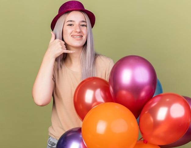 Lächelndes junges schönes mädchen, das zahnspangen mit partyhut trägt, der hinter ballons steht und telefonanrufgeste zeigt