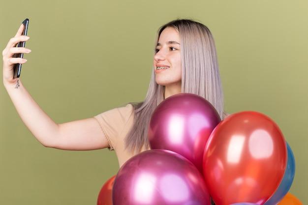 Lächelndes junges schönes mädchen, das zahnspangen trägt und das telefon hält und betrachtet, das hinter ballons steht