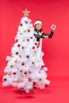 Lächelndes junges schönes mädchen in einem schwarzen kleid mit weihnachtsmannhut, der sich hinter weihnachtsbaum versteckt