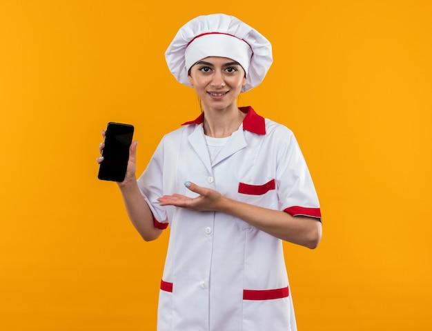 Lächelndes junges schönes mädchen in kochuniform hält und zeigt auf das telefon isoliert auf orangefarbener wand