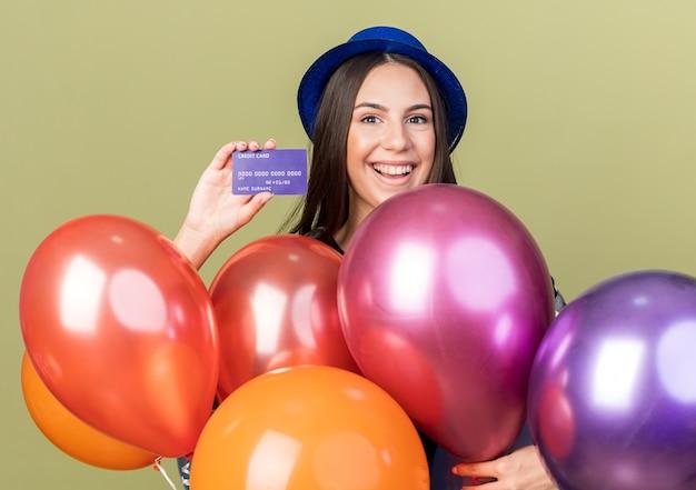 Lächelndes junges schönes mädchen mit blauem hut, das hinter ballons steht und kreditkarte isoliert auf olivgrüner wand hält