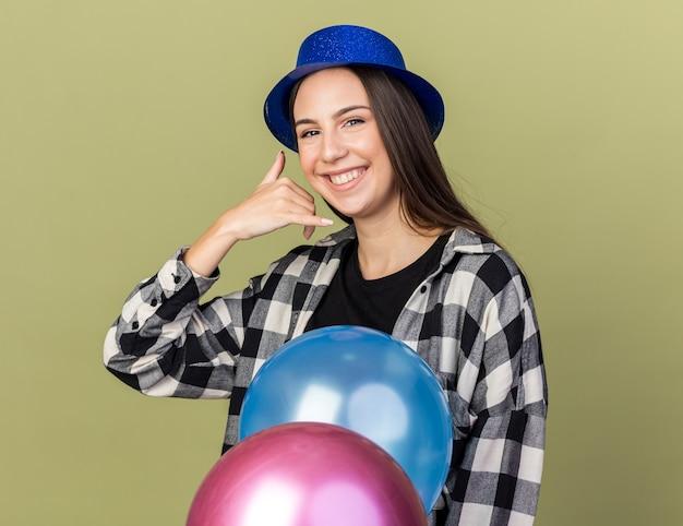 Lächelndes junges schönes mädchen mit blauem hut, das hinter ballons steht und telefonanrufgeste zeigt