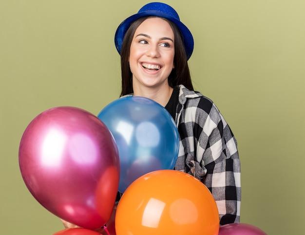 Lächelndes junges schönes mädchen mit blauem hut, das hinter ballons steht