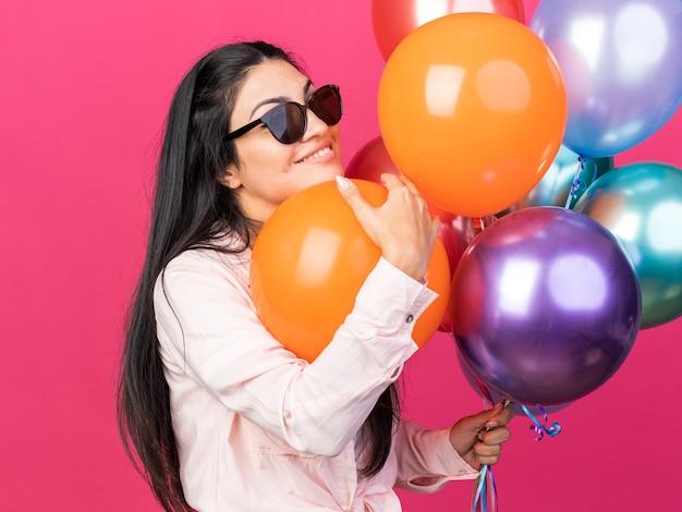 Lächelndes junges schönes mädchen mit brille mit ballons