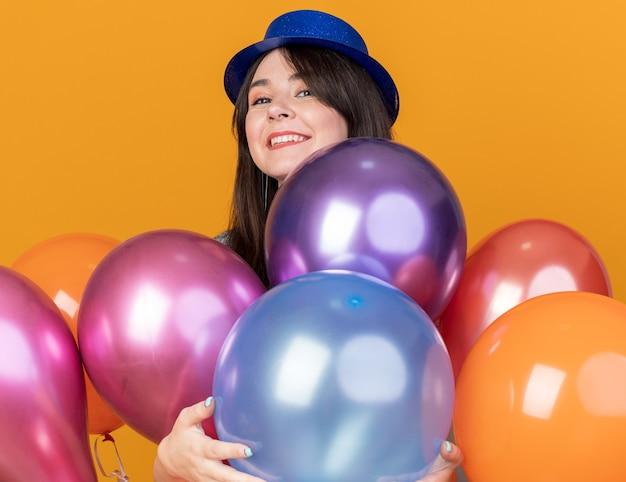 Lächelndes junges schönes mädchen mit partyhut, das hinter luftballons steht, isoliert auf orangefarbener wand
