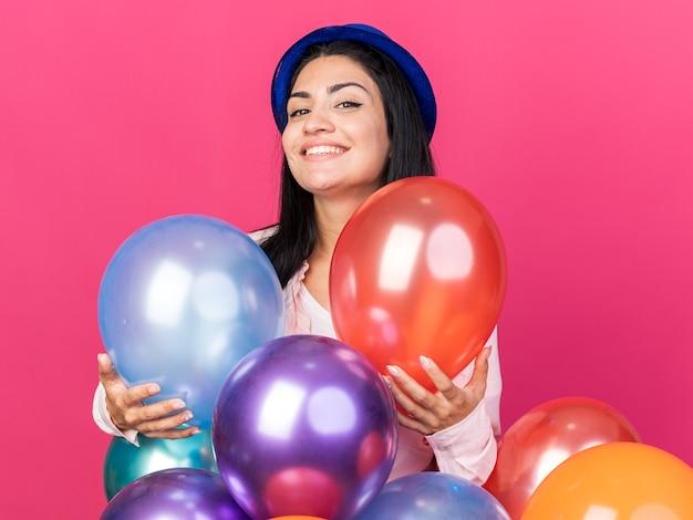 Lächelndes junges schönes mädchen mit partyhut, das hinter luftballons steht