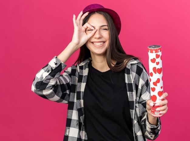 Lächelndes junges schönes mädchen mit partyhut, das konfettikanonen hält, die blickgeste einzeln auf rosa wand zeigen