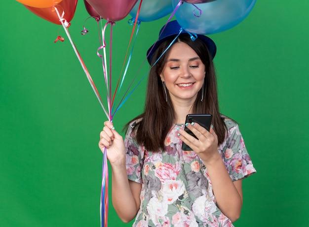 Lächelndes junges schönes mädchen mit partyhut, das luftballons hält und auf das telefon in der hand schaut, isoliert auf grüner wand
