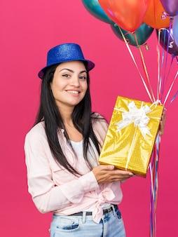 Lächelndes junges schönes mädchen mit partyhut, das luftballons mit geschenkbox hält