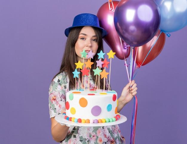 Lächelndes junges schönes mädchen mit partyhut, das luftballons mit kuchen hält, isoliert auf blauer wand