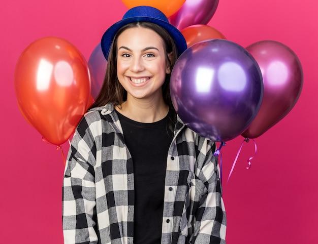 Lächelndes junges schönes mädchen mit partyhut, das vor ballons steht, isoliert auf rosa wand
