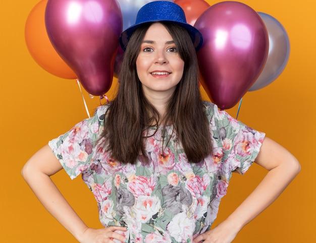 Lächelndes junges schönes mädchen mit partyhut, das vor ballons steht und die hände auf die hüfte legt, isoliert auf oranger wand
