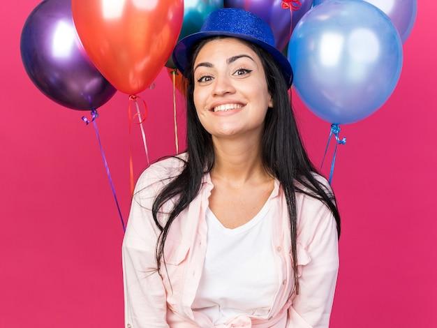 Lächelndes junges schönes mädchen mit partyhut, das vor ballons steht
