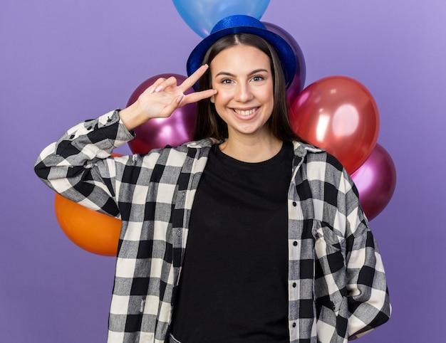 Lächelndes junges schönes mädchen mit partyhut, das vor luftballons steht und friedensgeste zeigt