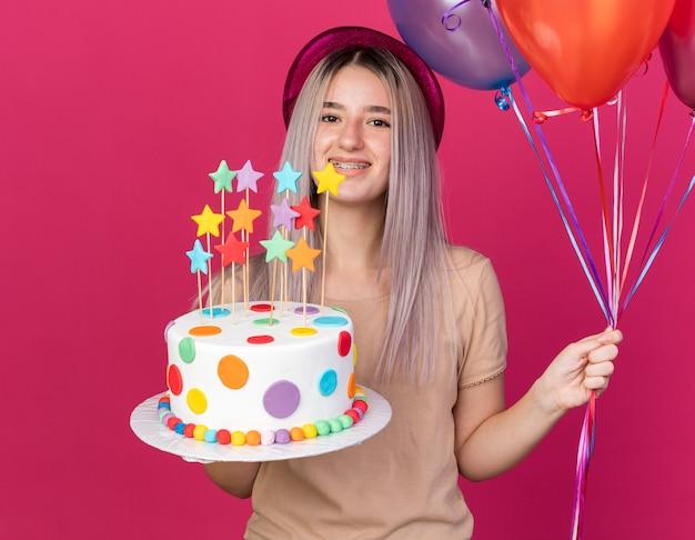 Lächelndes junges schönes mädchen mit partyhut mit zahnspangen, das luftballons mit kuchen hält