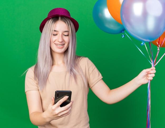 Lächelndes junges schönes mädchen mit partyhut und hosenträgern, das luftballons hält und auf das telefon in der hand schaut, isoliert auf grüner wand