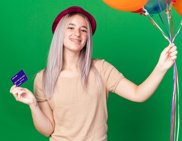 Lächelndes junges schönes mädchen mit partyhut und hosenträgern mit luftballons mit kreditkarte