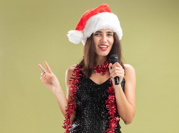 Lächelndes junges schönes mädchen mit weihnachtsmütze mit girlande am hals, das mikrofon hält und singt, die friedensgeste einzeln auf olivgrünem hintergrund zeigt showing