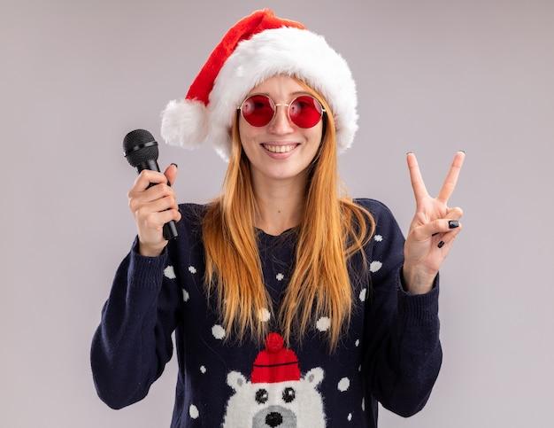 Lächelndes junges schönes mädchen mit weihnachtsmütze und brille mit mikrofon, das friedensgeste isoliert auf weißer wand zeigt