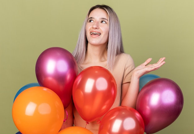 Lächelndes junges schönes mädchen mit zahnspangen, das hinter ballons steht und die hand isoliert auf olivgrüner wand ausbreitet