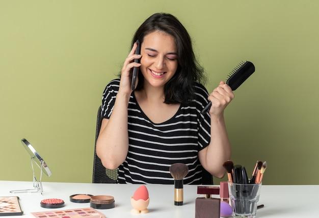 Lächelndes junges schönes mädchen sitzt am tisch mit make-up-tools, die kamm halten, spricht am telefon einzeln auf olivgrünem hintergrund