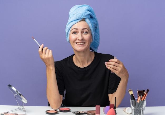Lächelndes junges schönes mädchen sitzt am tisch mit make-up-tools und wischt die haare im handtuch ab, das lipgloss auf blauem hintergrund hält