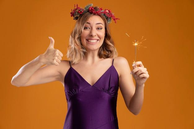 Lächelndes junges schönes mädchen trägt lila kleid mit kranz hält wunderkerzen mit daumen nach oben isoliert auf braunem hintergrund