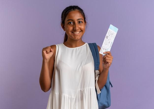 Lächelndes junges schulmädchen, das rückentasche hält ticket hält und ja-geste auf isoliertem purpur zeigt