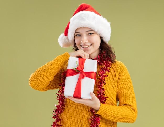 Lächelndes junges slawisches mädchen mit weihnachtsmütze und mit girlande um den hals, die weihnachtsgeschenkbox isoliert auf olivgrüner wand mit kopienraum hält