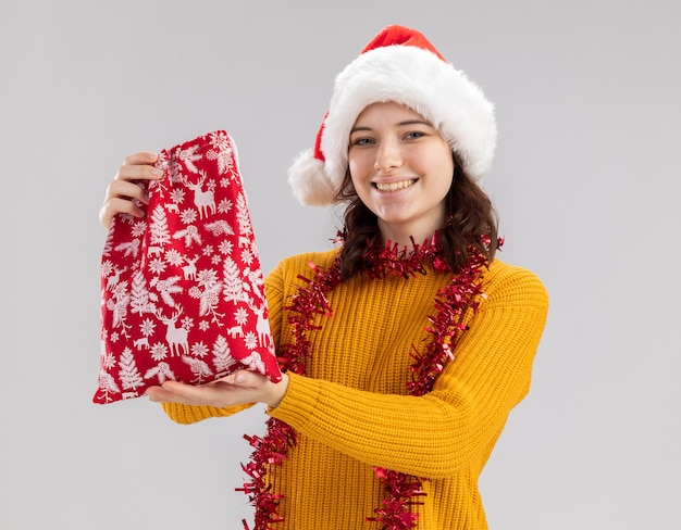 Lächelndes junges slawisches mädchen mit weihnachtsmütze und mit girlande um den hals hält weihnachtsgeschenktüte isoliert auf weißer wand mit kopierraum