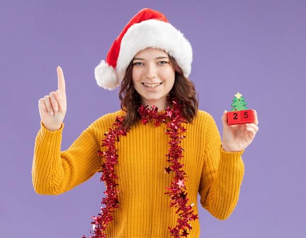 Lächelndes junges slawisches mädchen mit weihnachtsmütze und mit girlande um hals, der weihnachtsbaumverzierung hält und lokalisiert auf lila hintergrund mit kopienraum zeigt