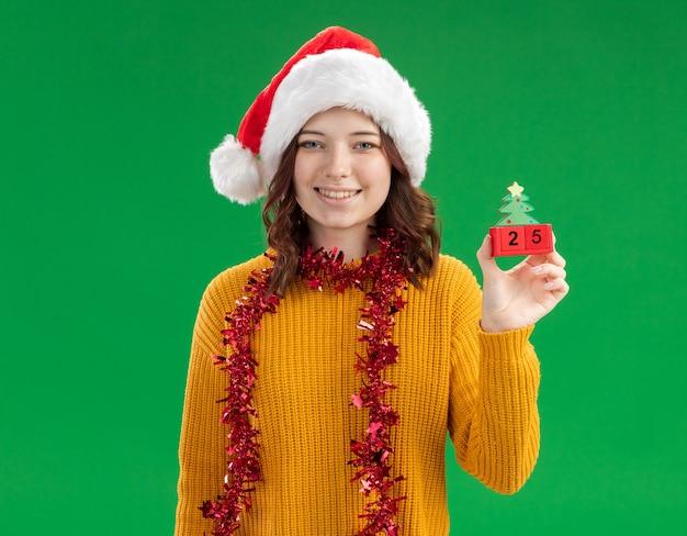 Lächelndes junges slawisches mädchen mit weihnachtsmütze und mit girlande um hals, der weihnachtsbaumverzierung hält