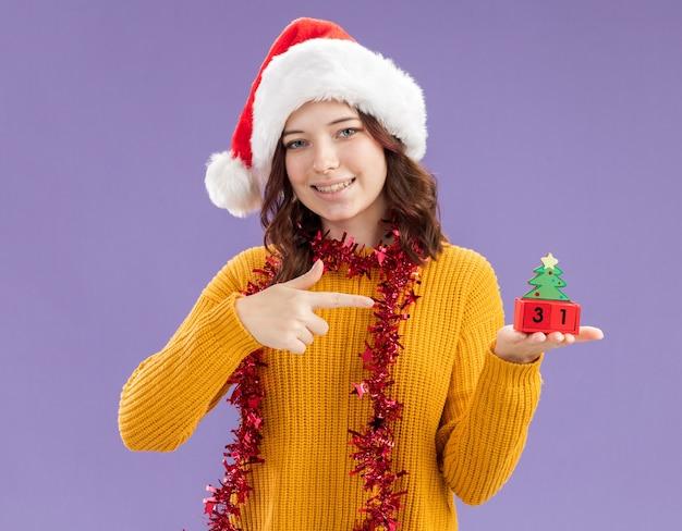 Lächelndes junges slawisches mädchen mit weihnachtsmütze und mit girlande um hals, die weihnachtsbaumverzierung hält und auf lila hintergrund mit kopienraum lokalisiert zeigt