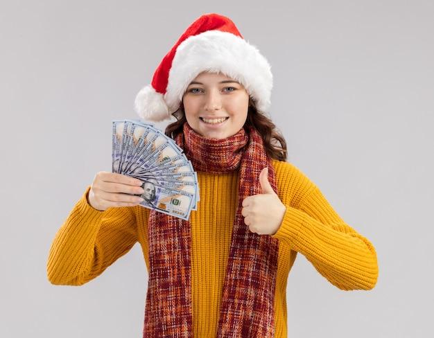 Lächelndes junges slawisches mädchen mit weihnachtsmütze und mit schal um den hals, das geld hält und isoliert auf weißer wand mit kopienraum daumen hochdrückt