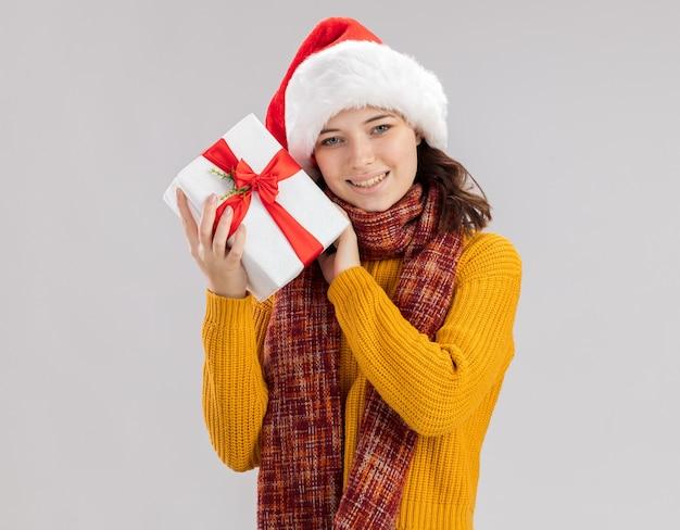 Lächelndes junges slawisches mädchen mit weihnachtsmütze und mit schal um hals, der weihnachtsgeschenkbox lokalisiert auf weißem hintergrund mit kopienraum hält