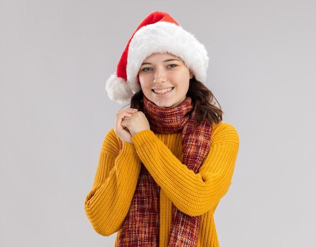 Lächelndes junges slawisches mädchen mit weihnachtsmütze und mit schal um hals hält hände zusammen und schaut