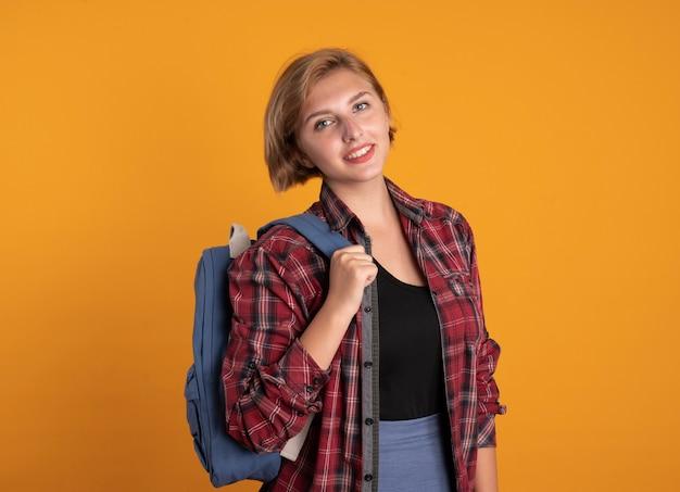 Lächelndes junges slawisches studentenmädchen, das rucksack trägt, schaut in die kamera